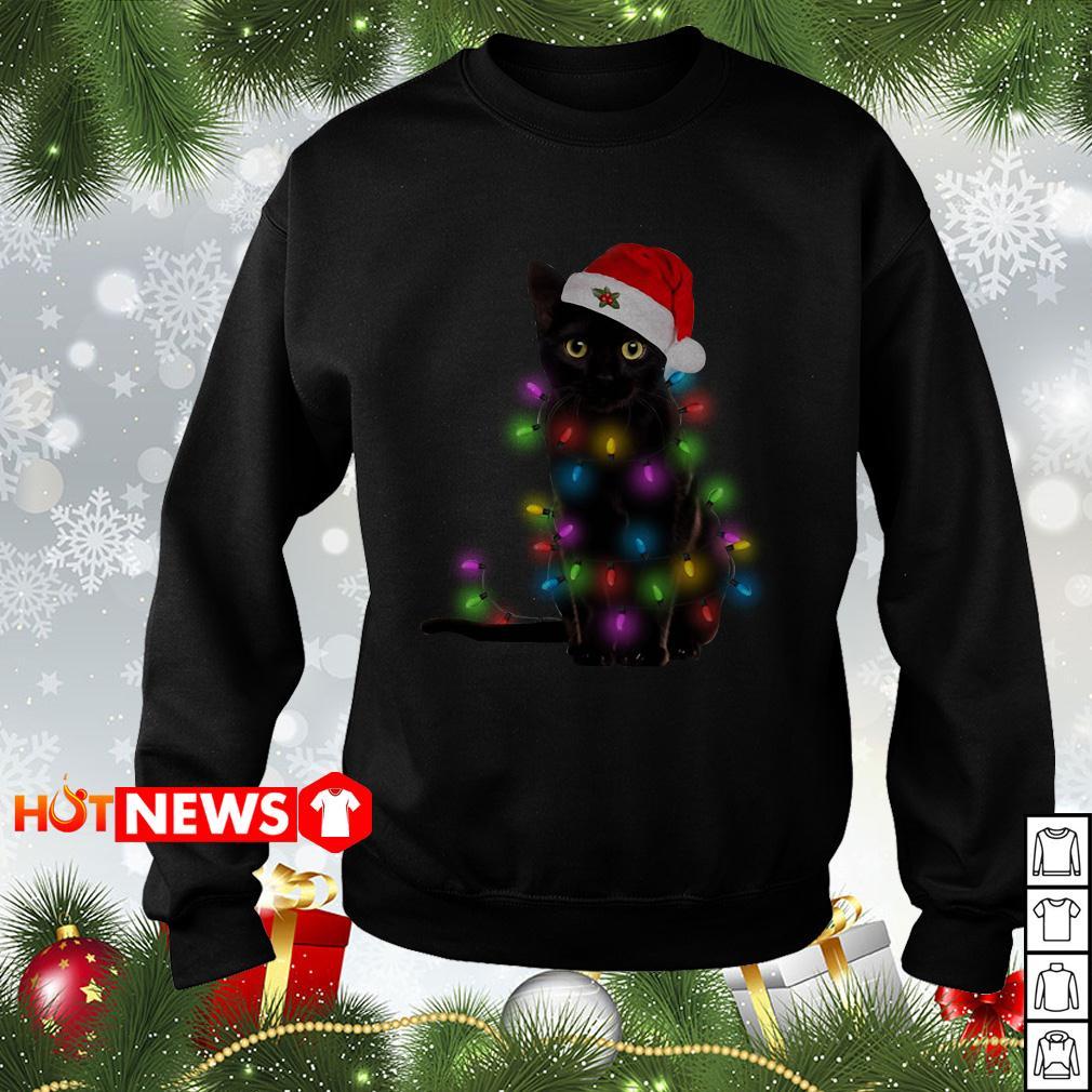 Black cat wearing Santa hat and light Christmas sweater